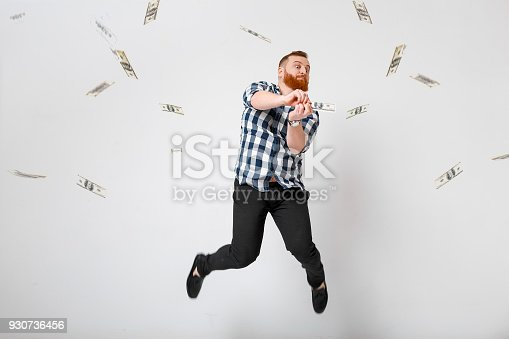 istock man standing under money rain 930736456