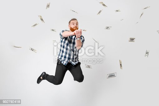 969671638istockphoto man standing under money rain 932792418