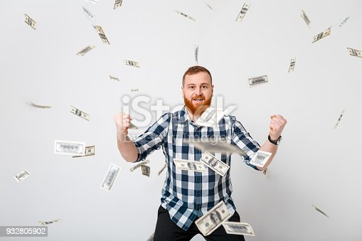 969671638istockphoto man standing under money rain 932805902