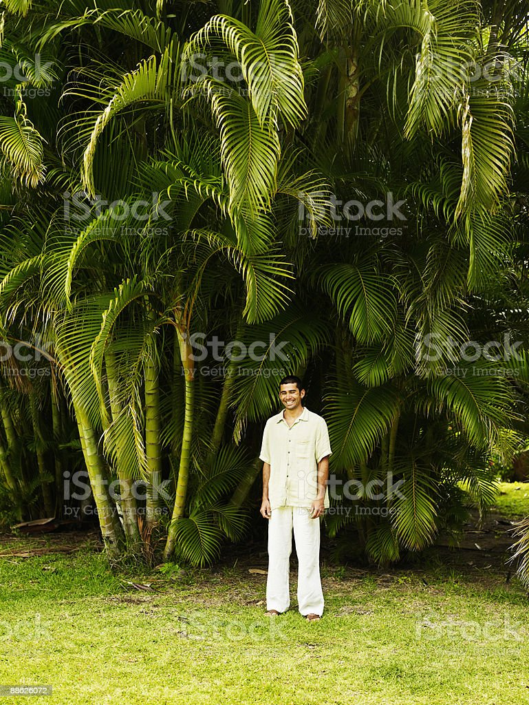 Man standing under palm trees laughing royalty-free stock photo