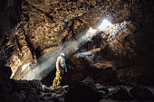 Man standing under the light in the mountain cave. Extreme adventure travel concept.