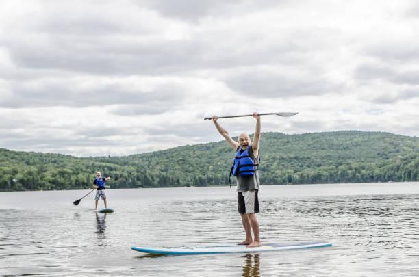 Mann oben auf Paddleboard auf einem See Sommer tagsüber – Foto