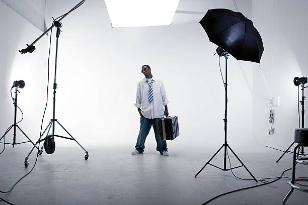 A man standing with a case in a white studio with lighting stock photo