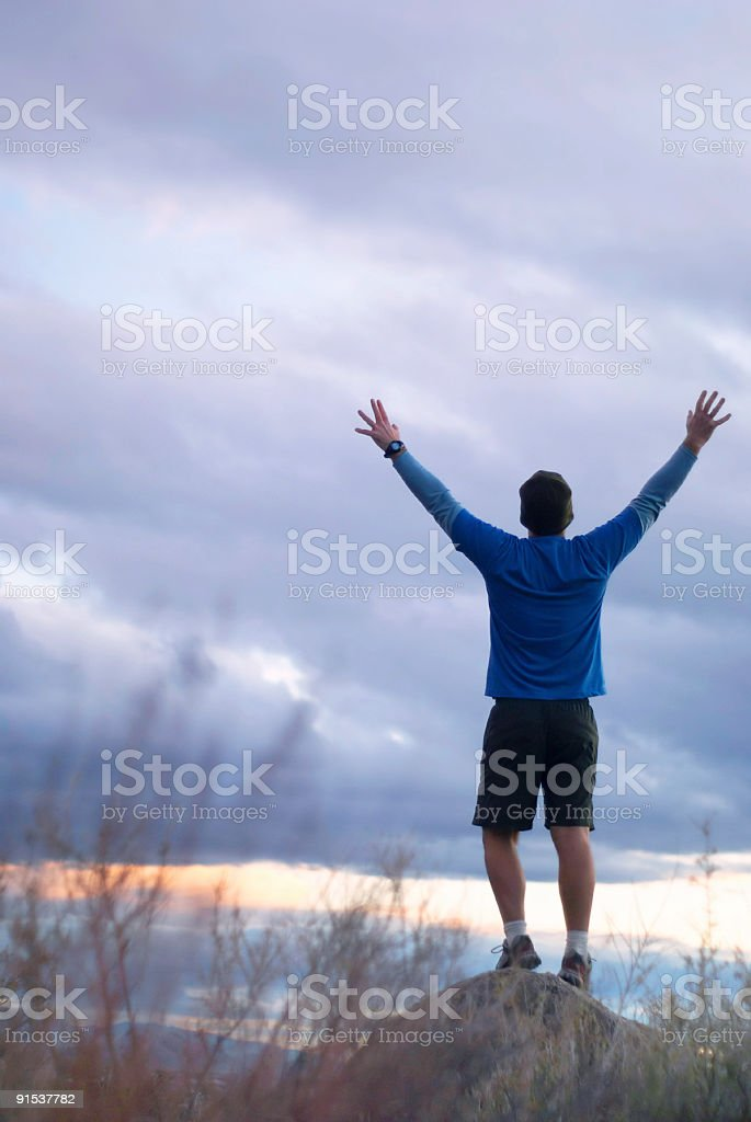 man standing with arms raised high into twilight sky royalty-free stock photo