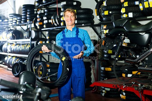 Handsome working man standing with new tires for motorbike in hands in shop