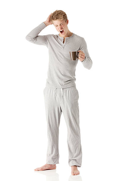 man standing with tea cup - pajamas stock photos and pictures