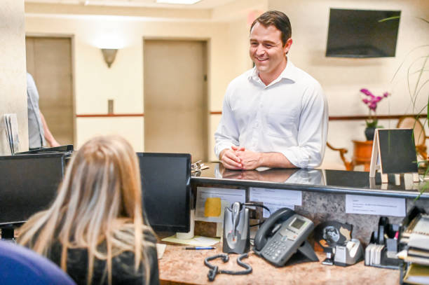 Man stands at at reception desk and talks to a receptionist in an office setting stock photo