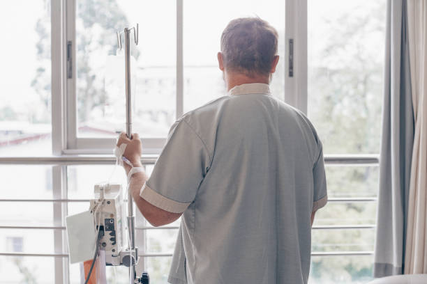 A man stands in a hospital ward and looks out the window. Dropper in a mans hand in a hospital A man stands in a hospital ward and looks out the window. Dropper in a mans hand in a hospital infused stock pictures, royalty-free photos & images