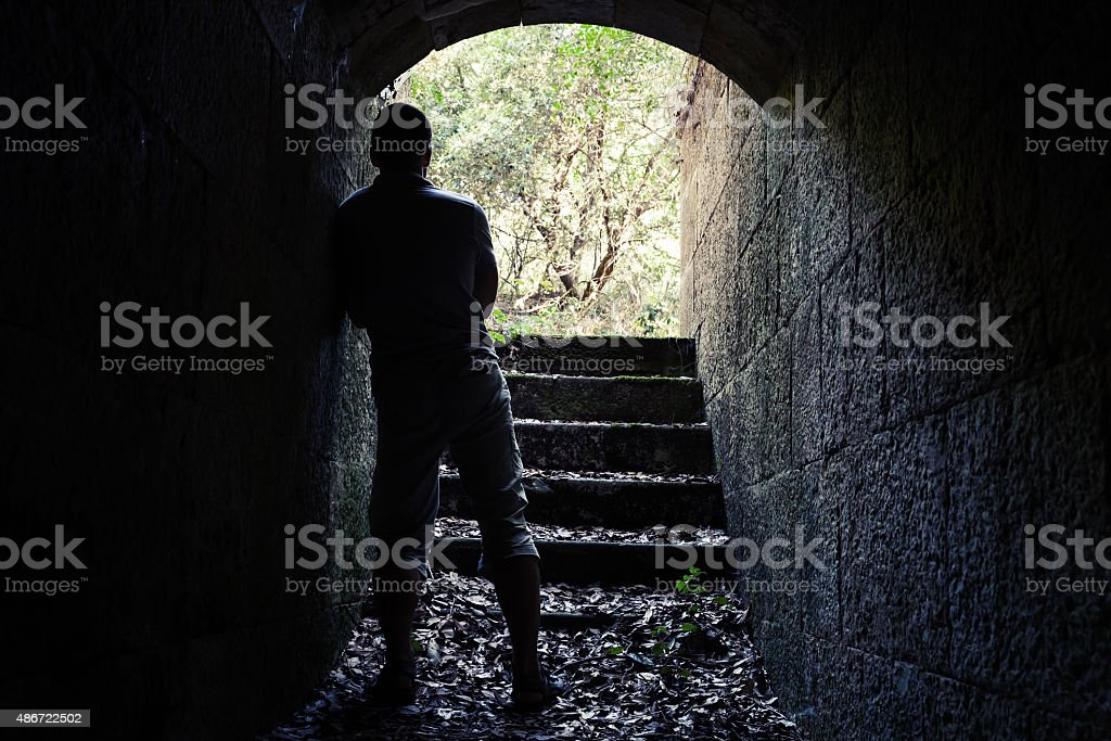Man stands in dark stone tunnel with glowing end royalty-free stock photo
