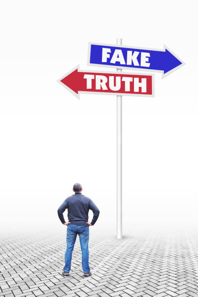 Man stands in front of a road sign pointing the direction to opposite sides to the fake and to the truth Man stands in front of a road sign pointing the direction to opposite sides to the fake and to the truth antipode stock pictures, royalty-free photos & images