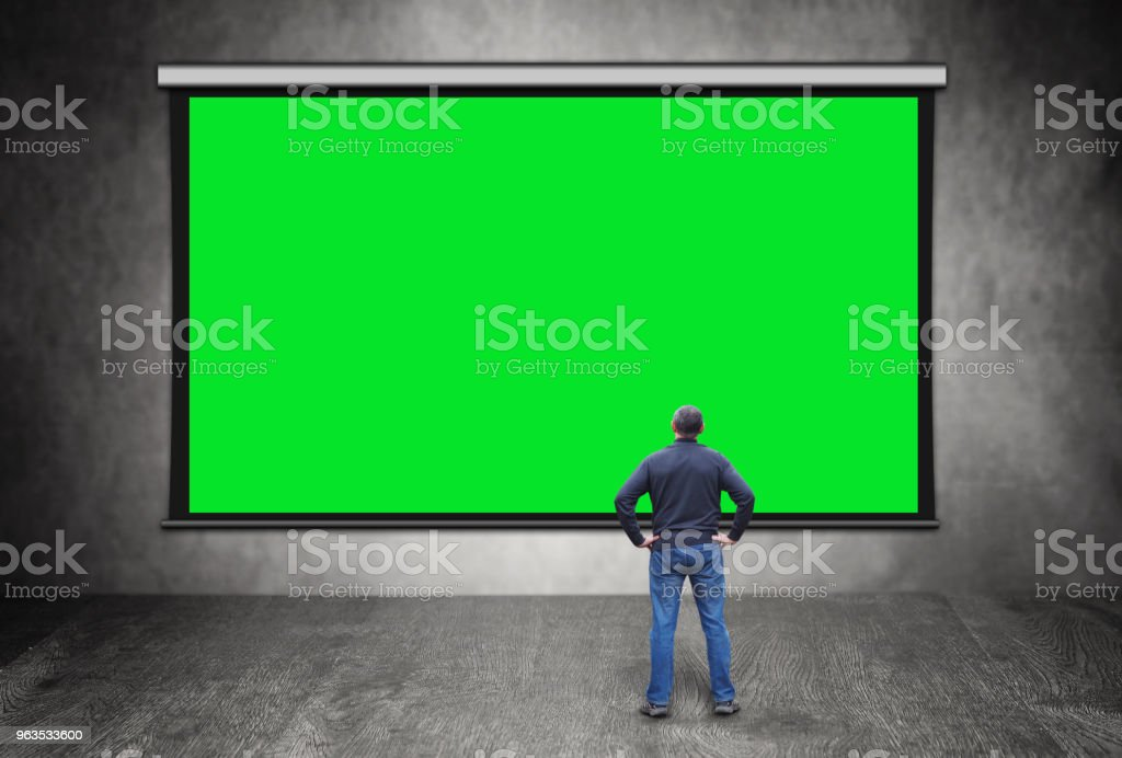 Man stands in front of big empty green screen stock photo