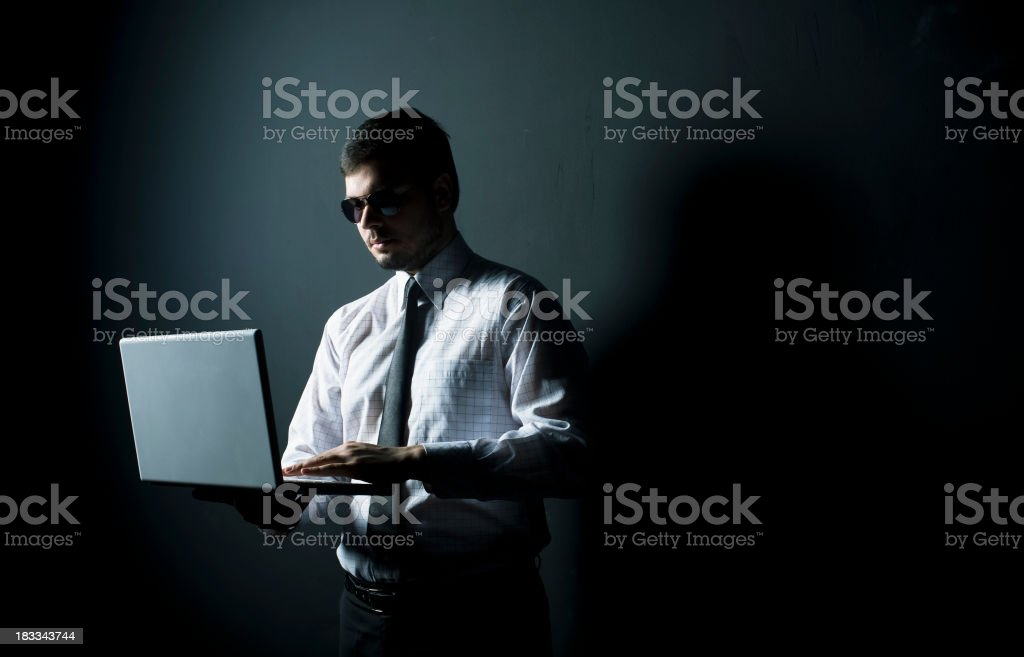 Man stands in the dark wearing sunglasses while on a laptop royalty-free stock photo
