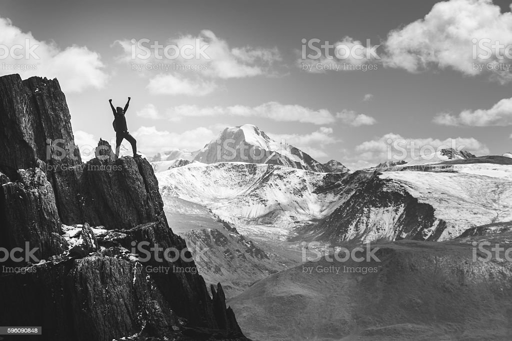 Man stands in winner pose on the cliff. Greyscale royalty-free stock photo
