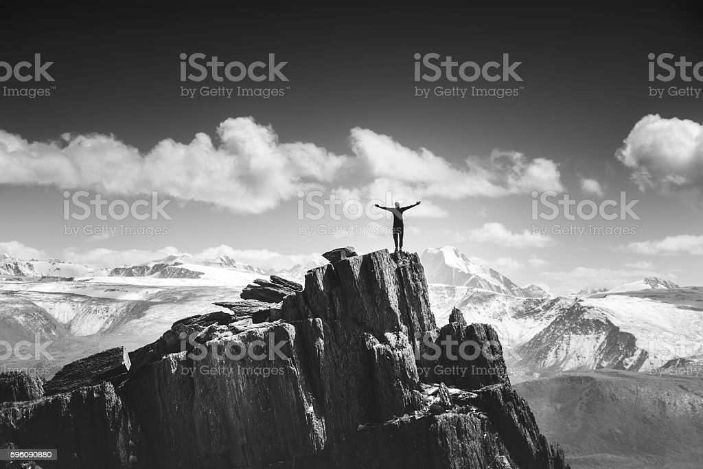 Man stands in winner pose on the top of mountain royalty-free stock photo