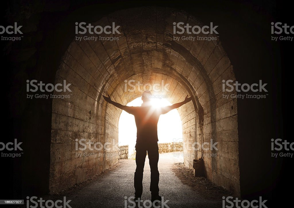 Man stands inside of old dark tunnel with shining sun stock photo
