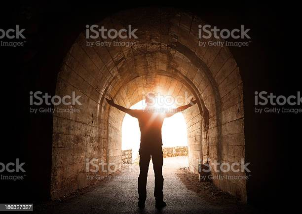 Man Stands Inside Of Old Dark Tunnel With Shining Sun Stock Photo - Download Image Now