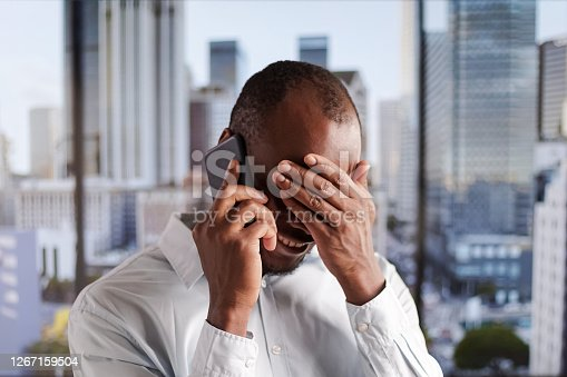 A man stands near a panoramic window with a view of the city and talks on the phone
