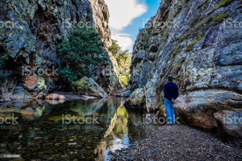 man stands near waterfall, Portugal. Concept: discovery