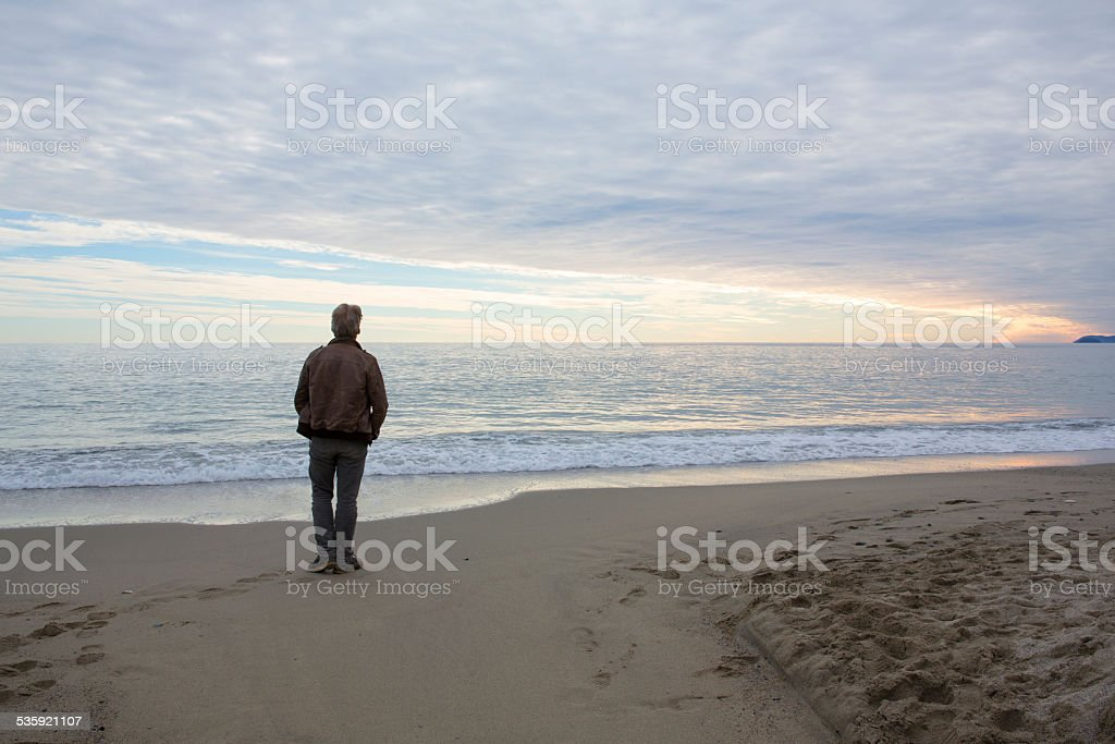 Man stands on beach under dome of clouds stock photo