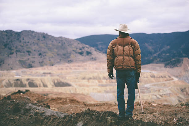 Man stands on mound of work site looking at mountains stock photo