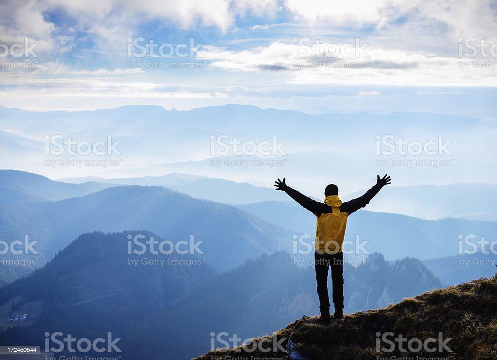 Man stands on mountain with arms raised above head stock photo
