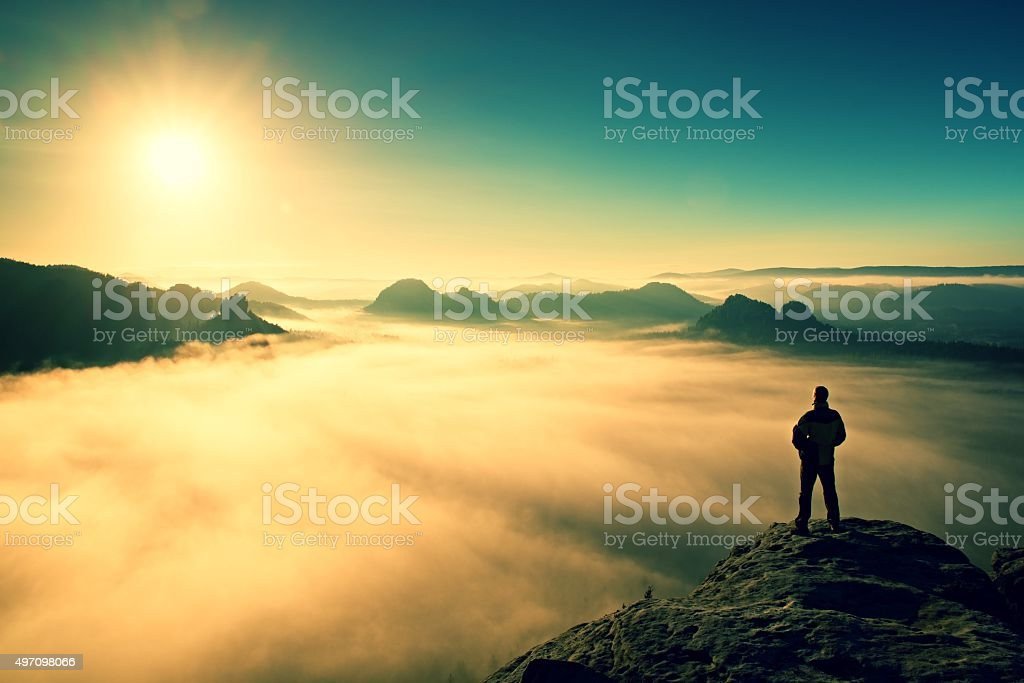 Man stands on peak of rock. Beautiful miracle of nature stock photo