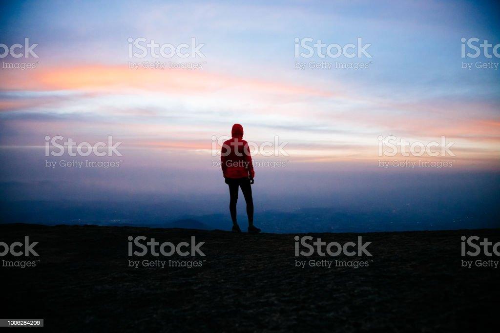 Homem fica no pico do estado Natural monumento de Pedra Grande, Atibaia, Brasil, por do sol com windstopper rosa. Silhueta de um homem caminhando no topo da montanha olhando para o horizonte. - foto de acervo