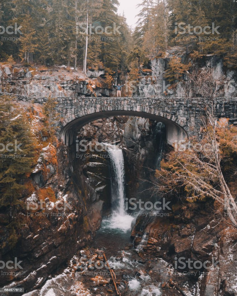 Man Stands on Stone Bridge Over Waterfall in Mount Rainier National Park stock photo
