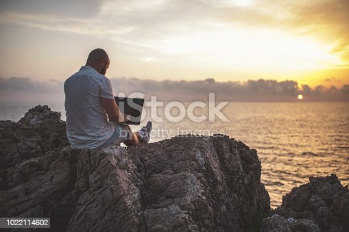 Man stands on the rocks at the sea and enjoys a sunset