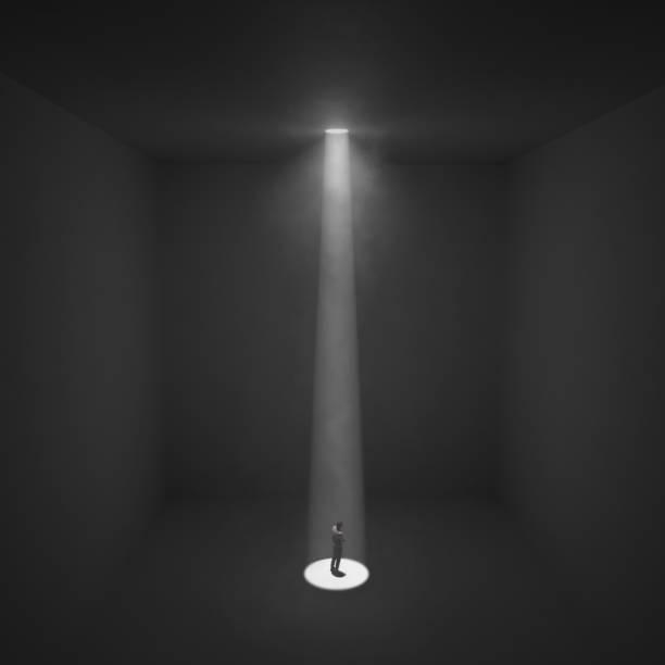 Der Mensch steht unter dem Lichtstrahl in einem dunklen Raum, – Foto