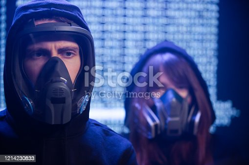 A man stands wears a protective mask and a woman in a gas mask stands behind him