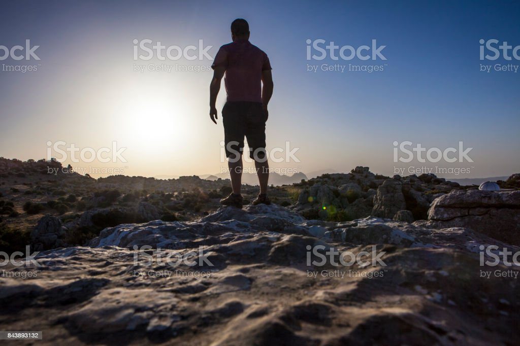 Man staring at sunrise over rocky ground. Torcal Natural Park, Malaga, Spain stock photo