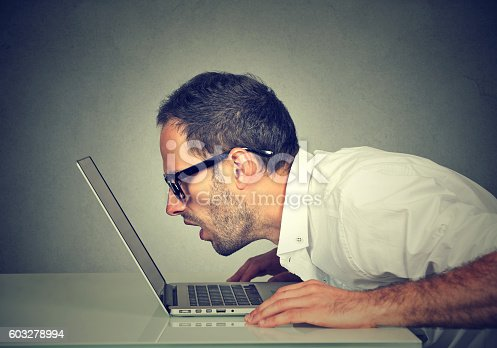 istock man staring closely intensely at laptop screen 603278994
