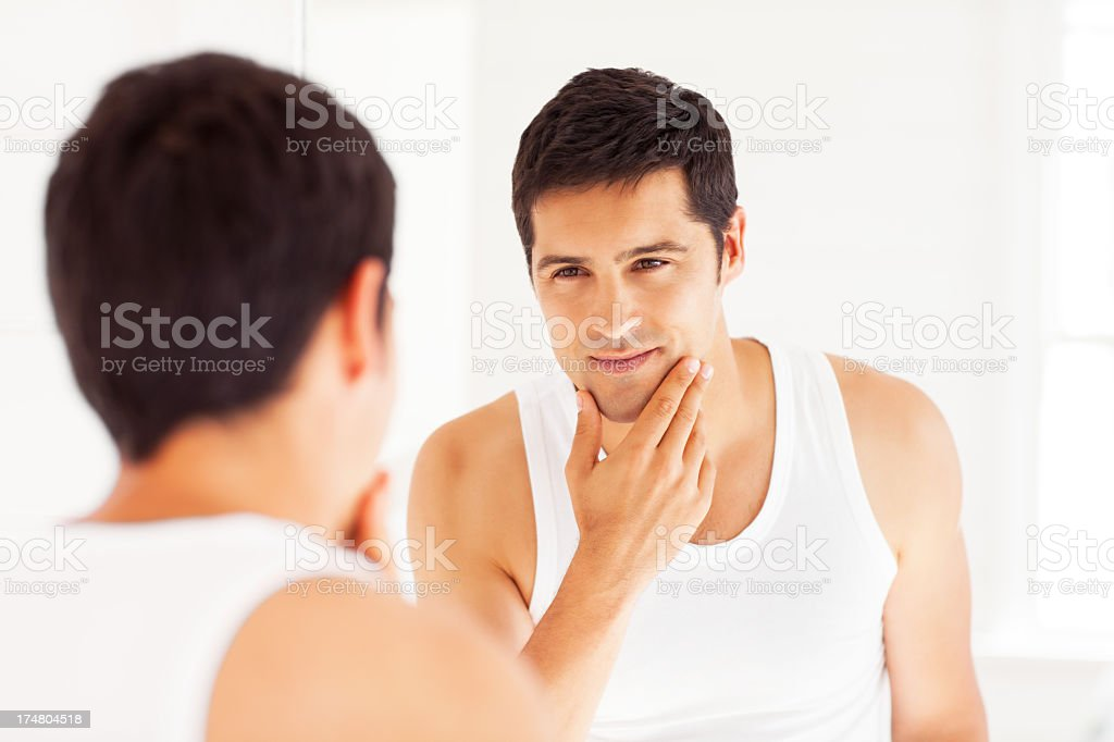A man staring himself in the mirror stock photo