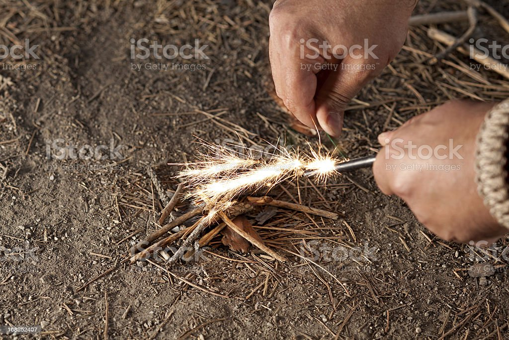 Man starting fire with ember and twigs stock photo