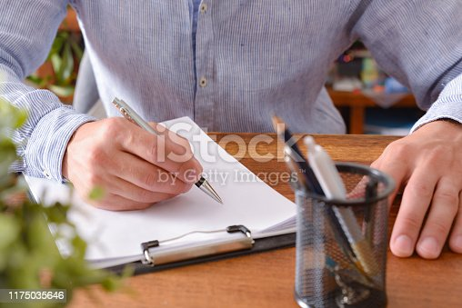 881192038 istock photo Man starting to write on blank sheet 1175035646
