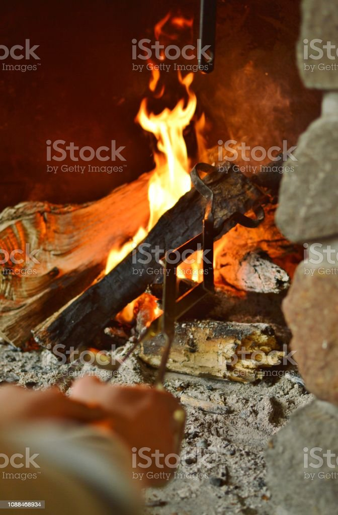 Man Starting Up The Fire In The Fireplace With Tongs On The Wood