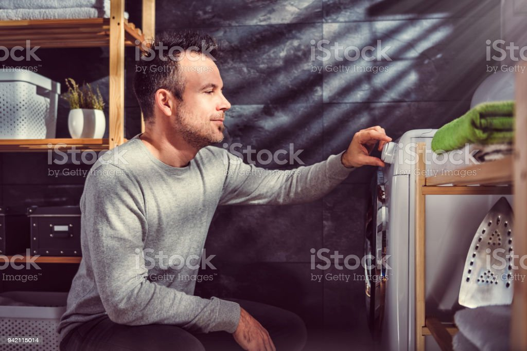 Man starting washing machine stock photo