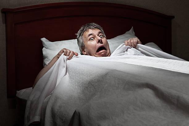 mann erschreckter wach von intruder - marvel schlafzimmer stock-fotos und bilder