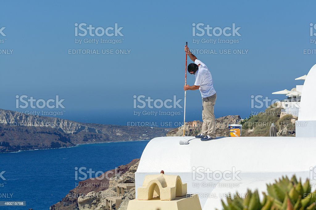 Man stays on the white roof and paints it stock photo