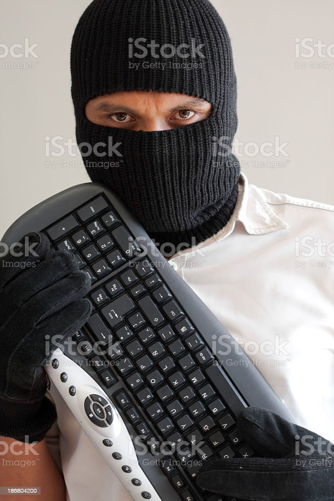 Man stealing data with keyboard royalty-free stock photo