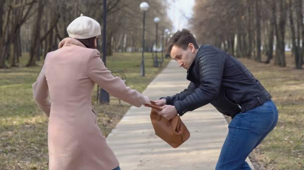 Mann stiehlt eine Frau Tasche aus einer Bank im park – Foto