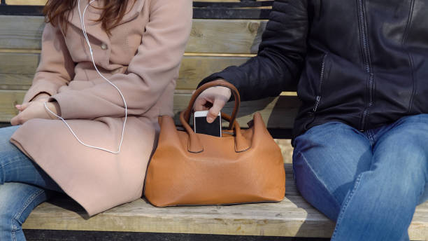Mann stiehlt das Telefon aus der Tasche einer Frau im park – Foto