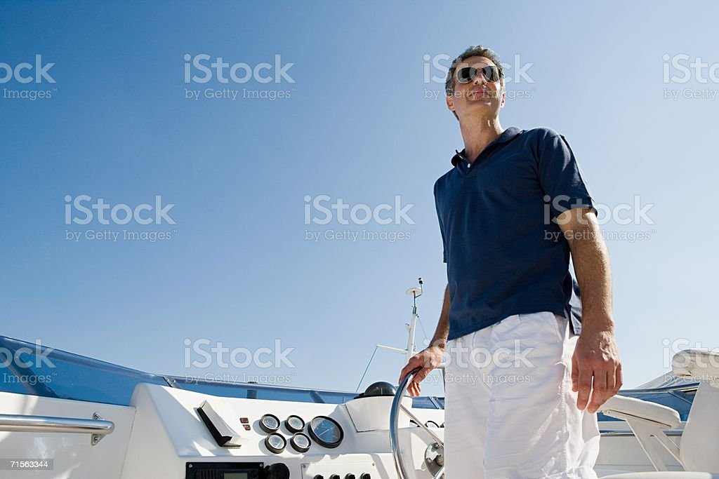 Man steering a yacht stock photo
