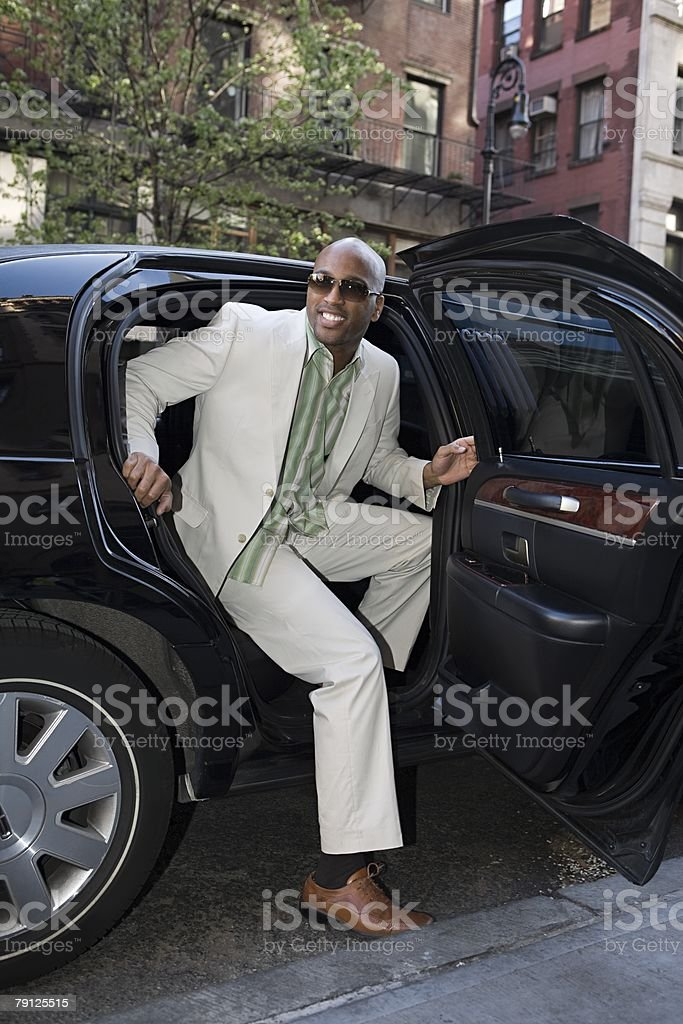 Man stepping out of limousine stock photo