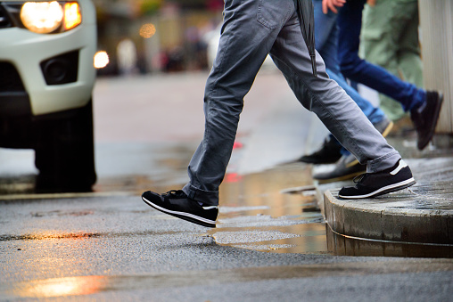 Man stepping over puddle in rain
