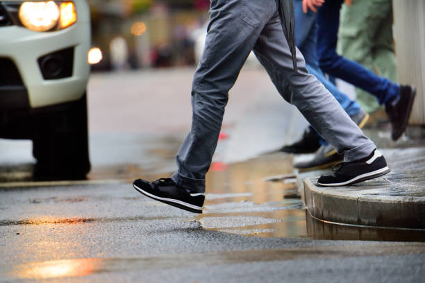 Man stepping over puddle in rain - foto stock
