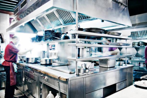 Man Stirring Pot in Stainless Steel Restaurant Kitchen stock photo
