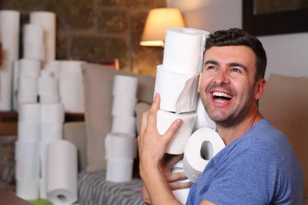 Homem estocando papel higiênico em casa - foto de acervo