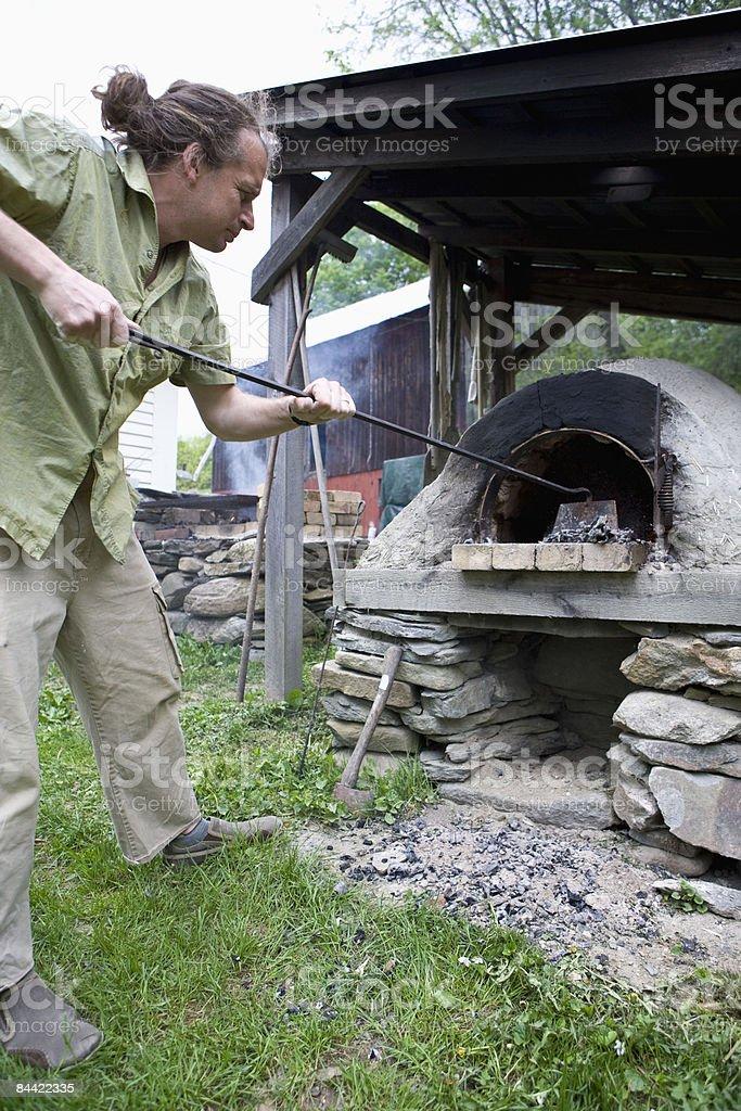 Man stoking outdoor stove royalty-free stock photo
